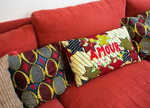 canapé rouge assorti avec des coussin en tissu wax